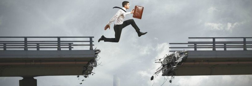 Man with briefcase jumping across broken bridge