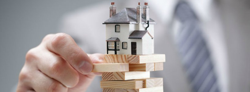 Business man playing jenga with house on top