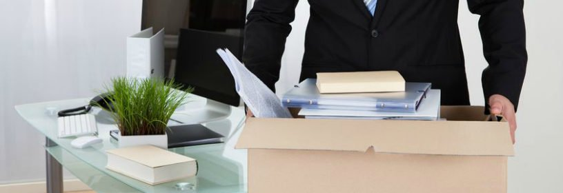 Man carrying box of items from desk