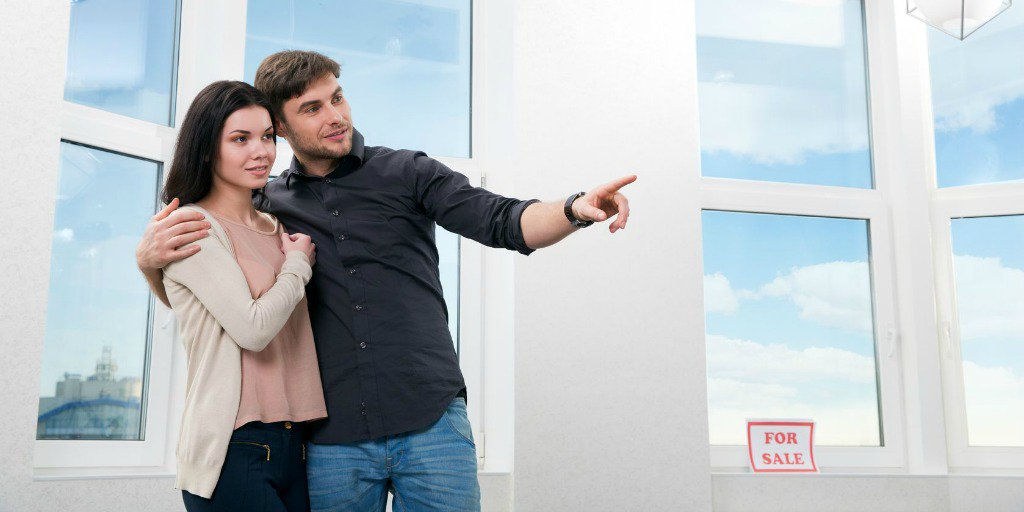 Happy couple pointing at feature of house
