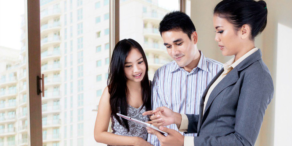 Couple looking at MLS on tablet with Agent