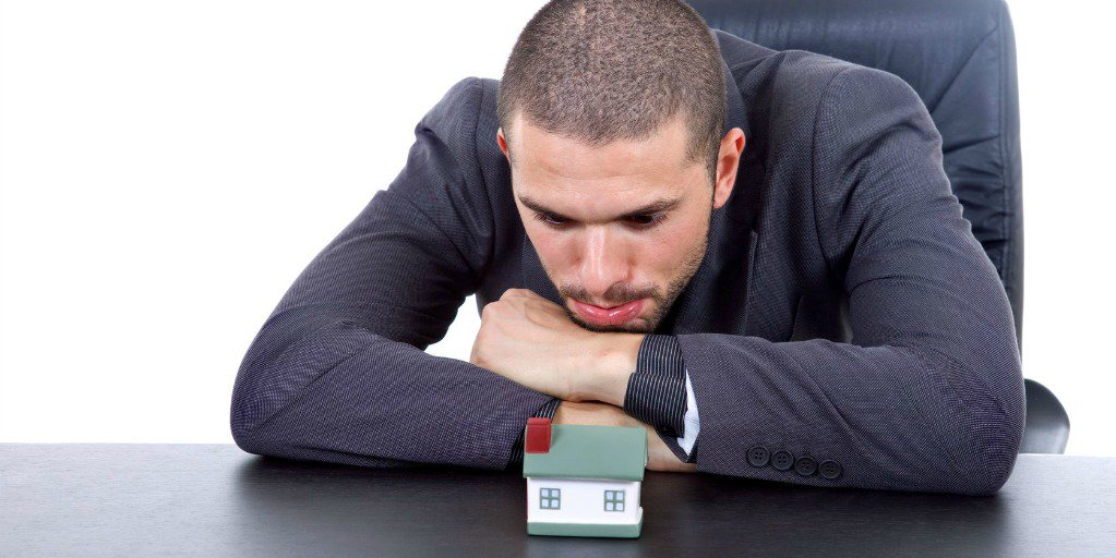 man staring blankly at model house