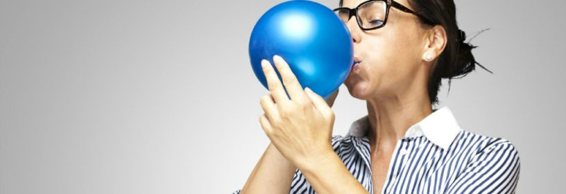 Woman blowing in balloon to expand it