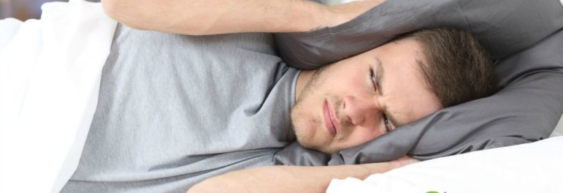 man in bed covering ears with pillow