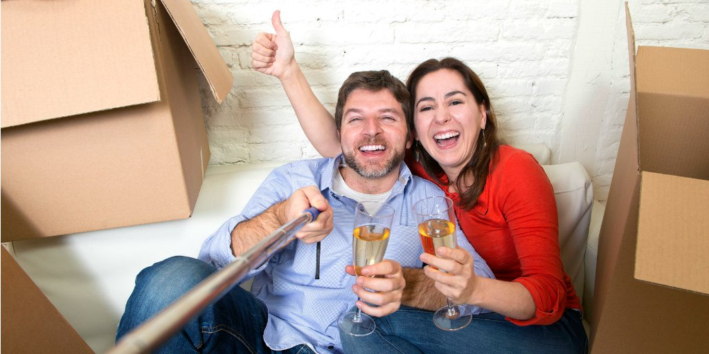 young couple drinking champagne with boxes in house