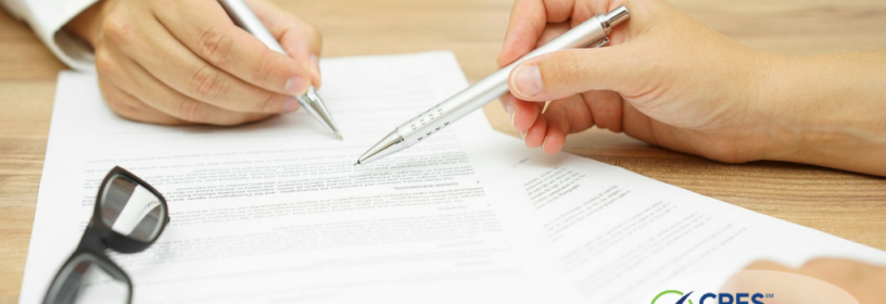 paperwork on a desk with two people pointing at it with pens