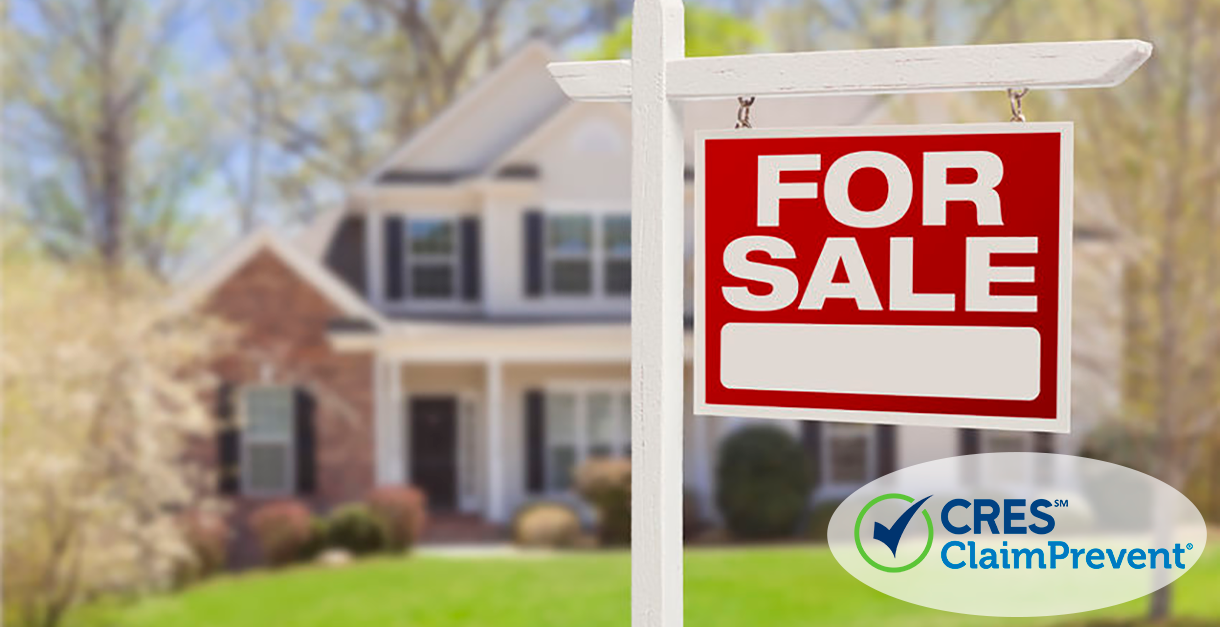 real estate for sale sign in front yard of house