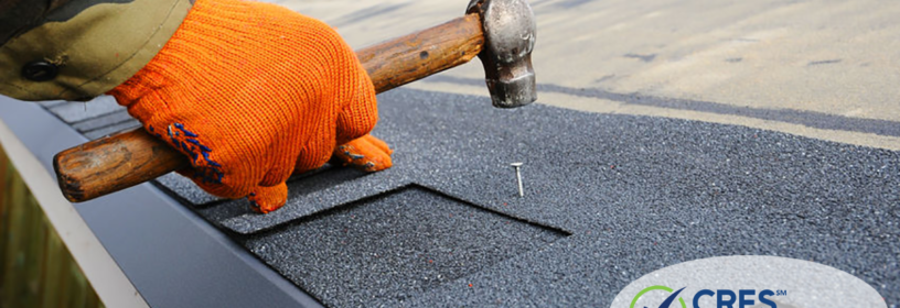 hand hammering nail into roof shingle