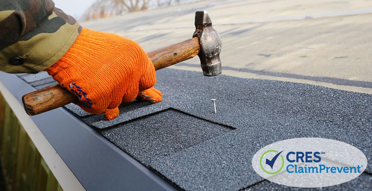 hand hammering nail into roof shingle