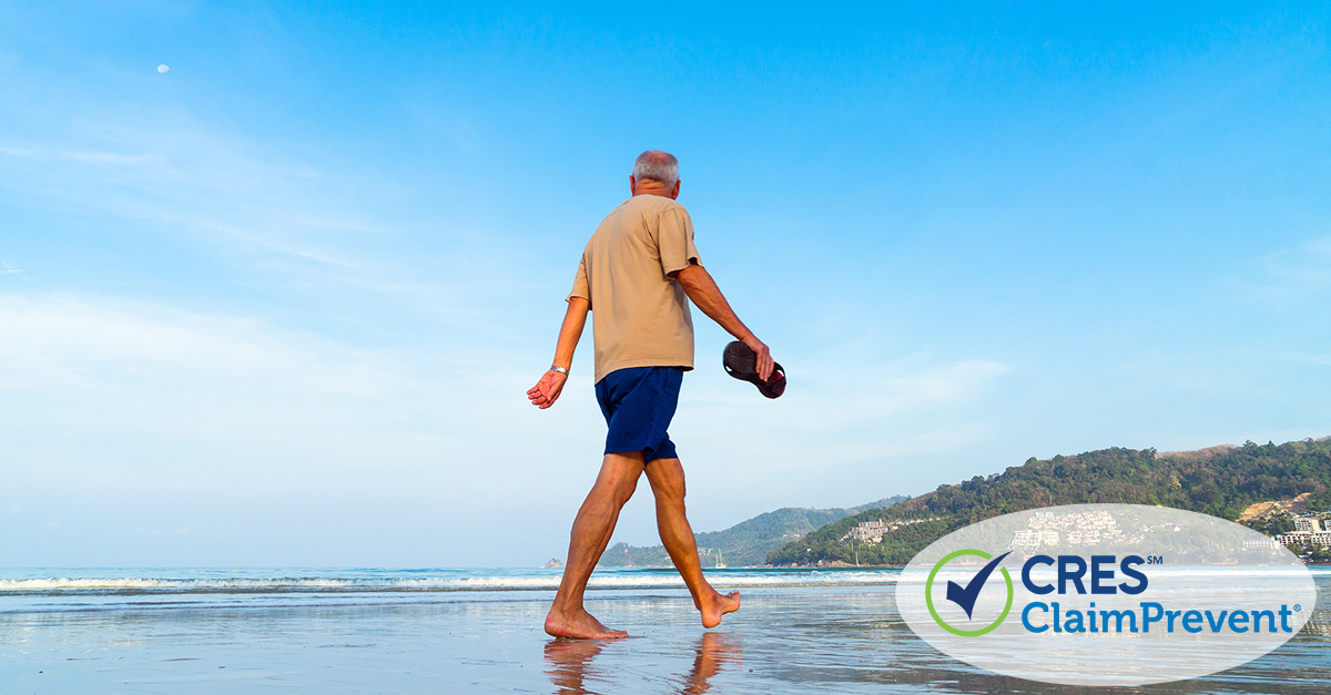 senior male holding flip flops walking along ocean edge with tree covered hills in the background