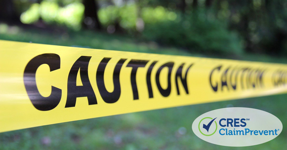 caution tape in front of green grass and trees