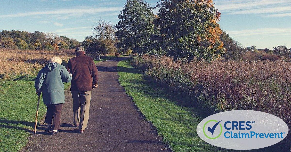 senior man and woman walking down sidewalk