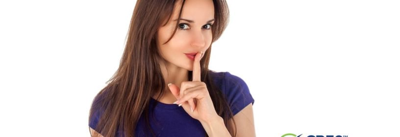 young woman with index finger in front of mouth representing shh