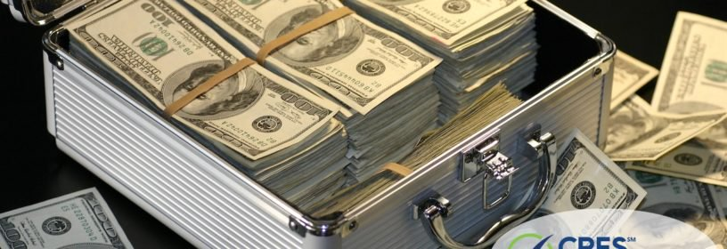 briefcase full of American hundred dollar bills and piles of cash around it