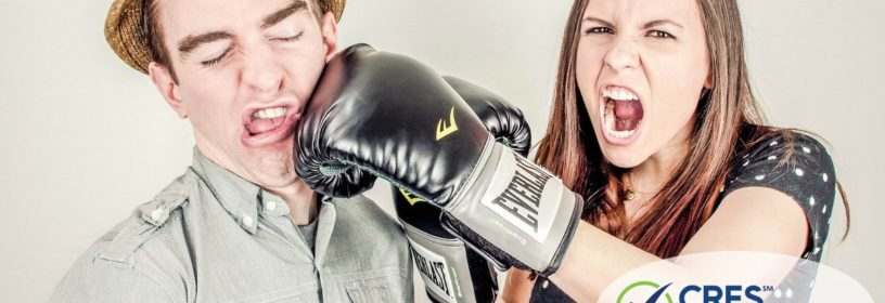 man getting punched by woman with boxing glove on