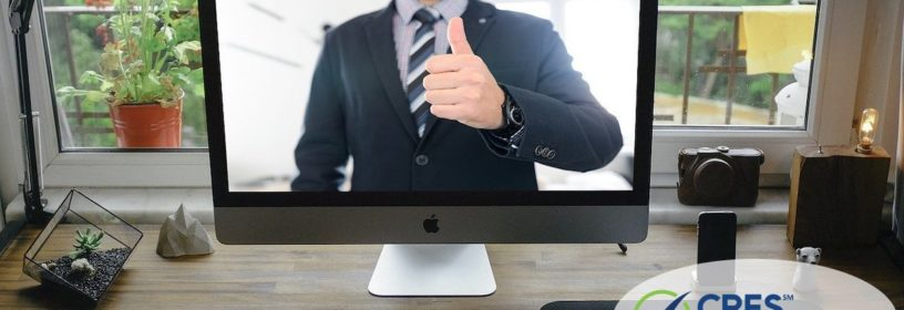home office with a computer screen image of man giving thumbs up