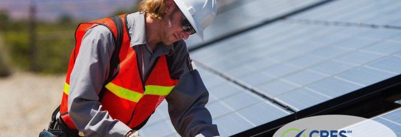 man fixing broken solar panel on house