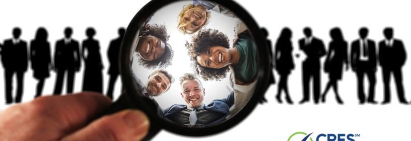 magnifying glass highlighting people from a group of shaded figures