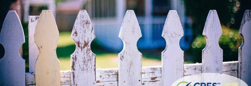 looking through white picket fence toward neighbors house