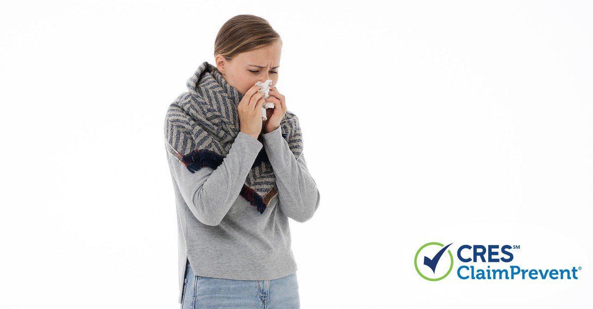 woman with gray sweater and scarf on sneezing into a tissue