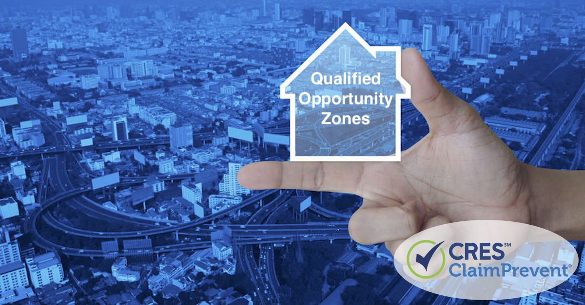 hand holding house concept image with qualified opportunity zones text overlaid on a cityscape