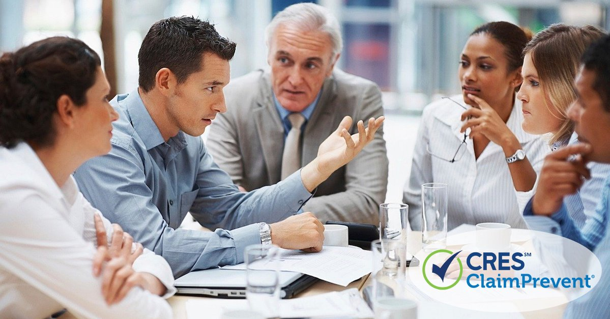 Five business professionals sitting around conference table having a discussion