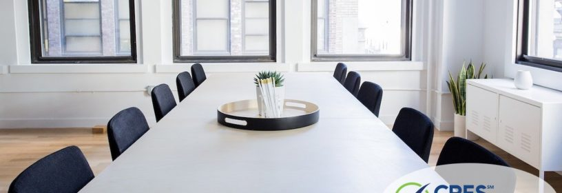 rectangular table in office space with empty chair surrounding it