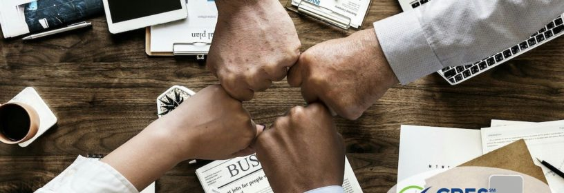 team members putting closed fists together over desk with business items
