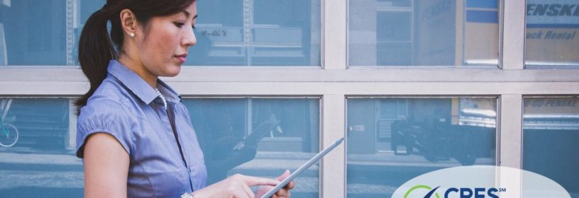 woman standing outside in front of building on ipad